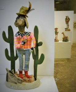 This piece is mixed media---it was constructed from clay, paper mache, acrylic paint, wood, nail polish, and cement.  I love the  challenge of working with a lot of different materials to achieve a certain look.  The feathers in his hat are feathers from out chickens here in San Antonio.  The red one is Aunt Mary's (God rest her soul) and the darker one is Bellina's.  She is very much alive and well and has begun to lay eggs!